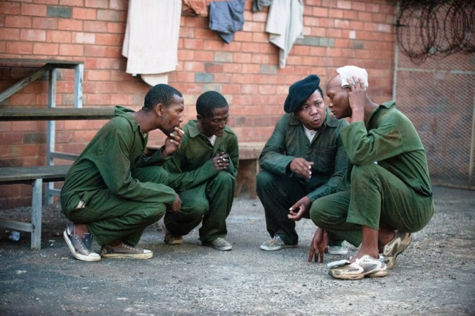 Pictured in the prison courtyard China Boy (Presley Chweneyagae) and Buttons (Warren Masemola) decide on Magadien's (Mothusi Magano) fate.